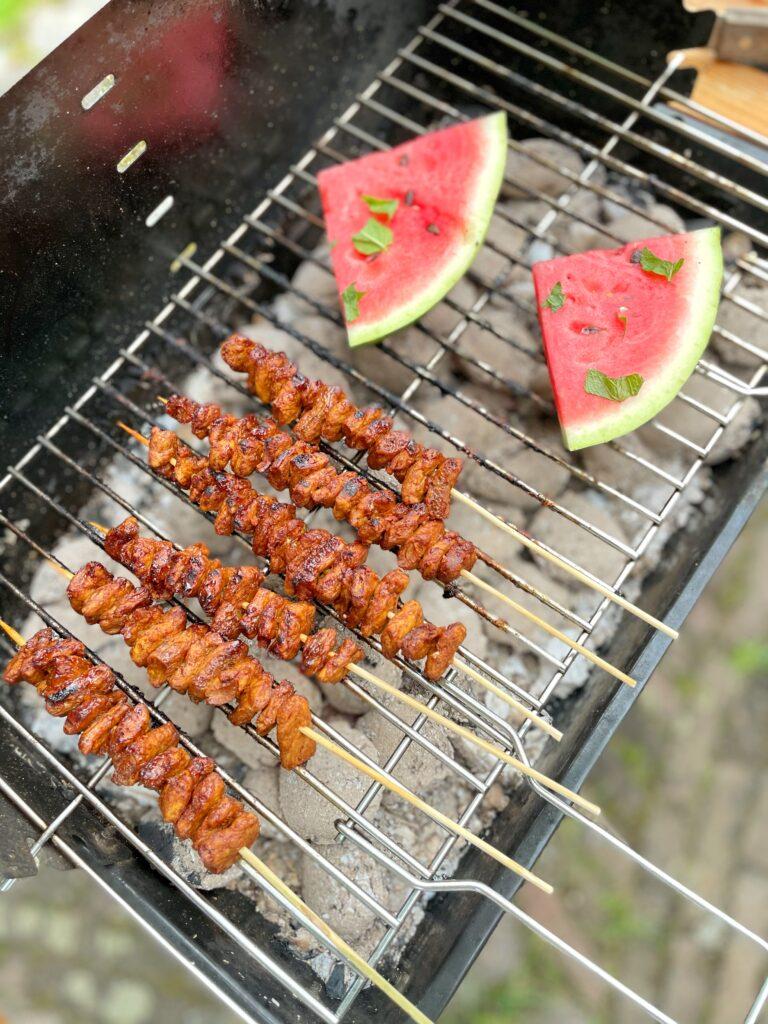 Barbecue met satéspiesjes van peas maker stukjes met meloen en munt