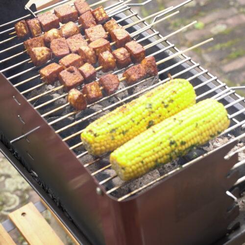 Op deze afbeelding staat een barbecue met daarop twee maiskolven en tempeh saté spiesjes