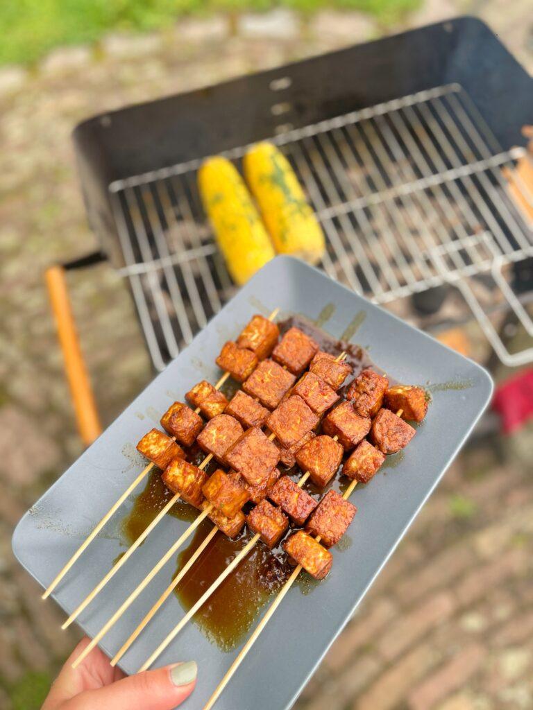 Een bord met gemarineerde tempeh satéspiesjes met op de achtergrond een barbecue met maiskolven erop.